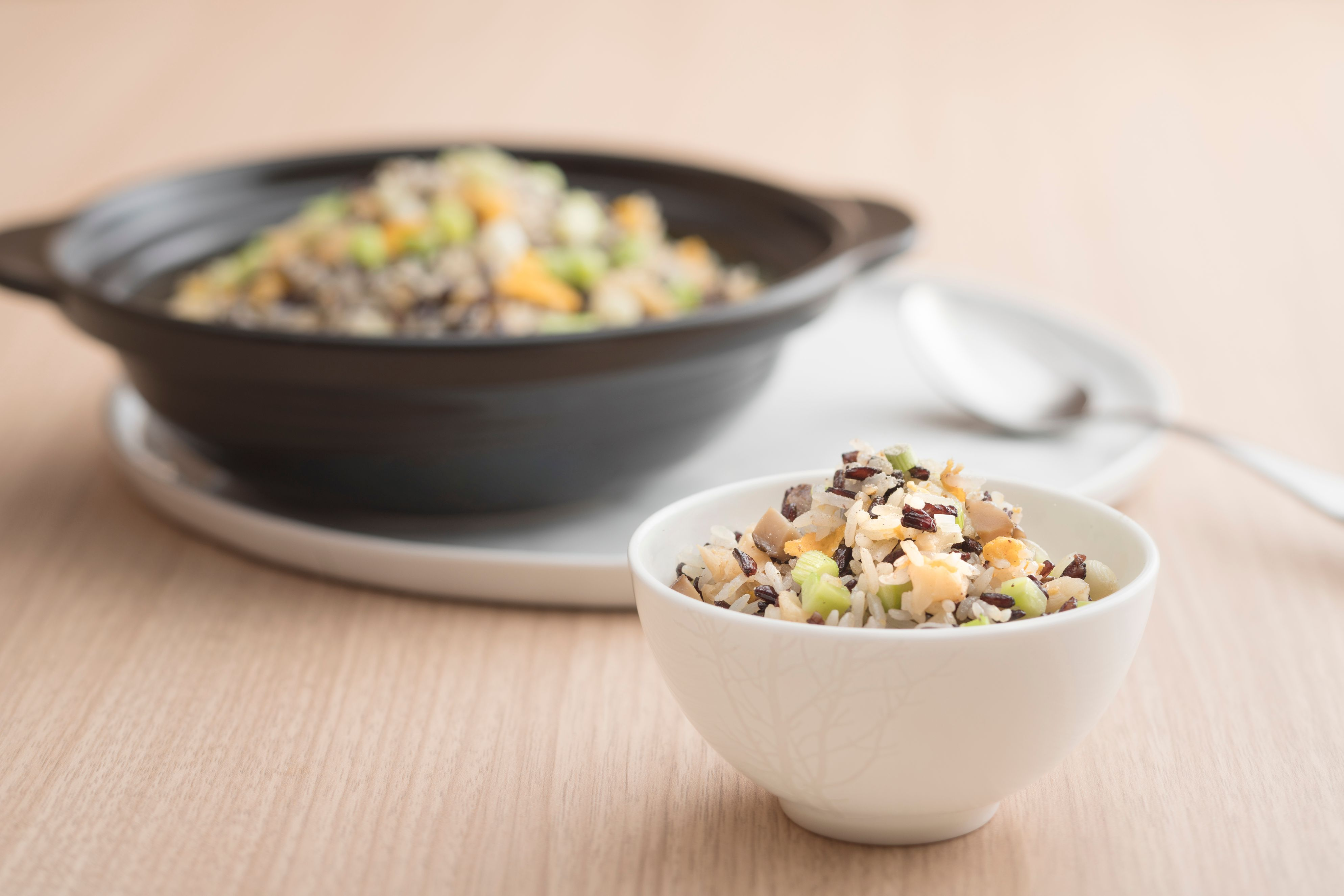 Fried brown rice with diced vegetables and pine nuts in claypot